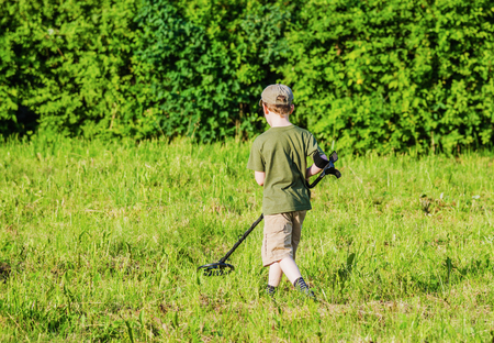 tresure: boy with a metal detector is moving away from the camera on the green grass on a summer evening