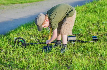 tresure: boy with a metal detector and shovel, he digs the ground looking for treasure