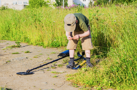 scavenge: boy with a metal detector looking for treasure Stock Photo