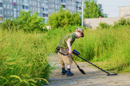 tresure: boy with a metal detector looking for treasure Stock Photo
