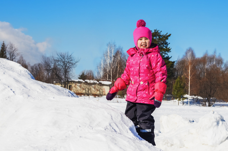 Joyful girl on a walk in  winters day. She stands on top of a mountain Stock Photo
