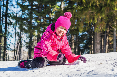 Little girl having fun on a walk on a winters day. She sits on top of the snow hill Stock Photo