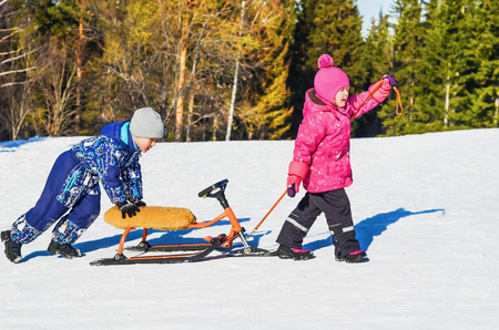 Children ride on a snow scooter on a bright Sunny winter day Stockfoto