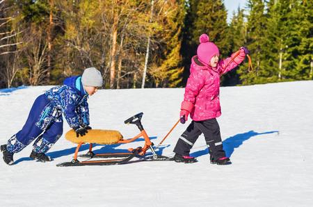 Children ride on a snow scooter on a bright Sunny winter day Foto de archivo