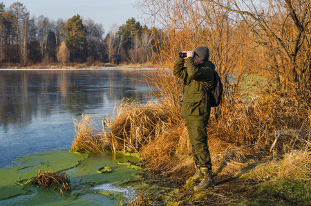 Man in tourist equipment stands on the shore of a frozen lake and looks through binoculars