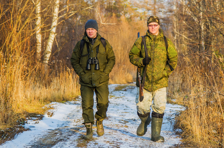 Two hunters walk along the forest road on a Sunny evening in late autumn Stock Photo - 96770438