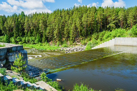 An old, unregulated dam on a Sunny summer day.  Russia, the river Neiva Stock Photo