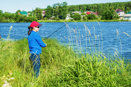 woman with a spinning rod catches a fish in the lake in summer day
