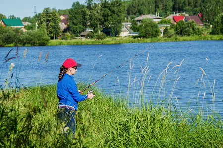 Woman with spinning fishing in the lake on a summer day