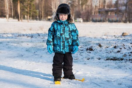 A little boy skiing on the first snow on a Sunny day