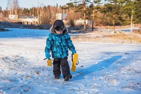 Happy little boy before a ski trip. He's holding skis Stock fotó