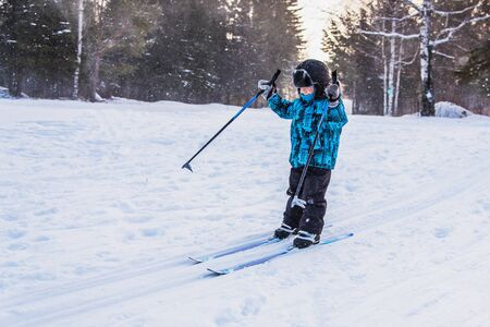 Happy little boy on a ski trip in the forest on a clear winter day. He's coming down from the snow hill
