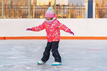 Little girl learns to skate on a winter evening