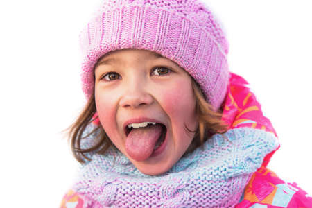 Portrait of a cheerful little girl. She's fooling around and sticking her tongue out. Close up