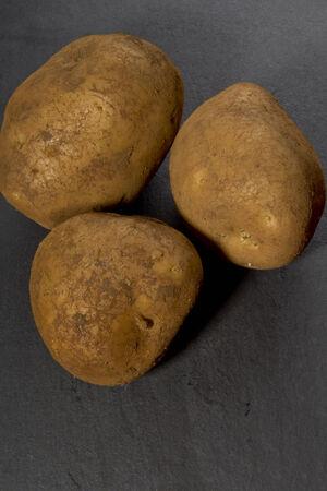 orla: Organic potatoes on slate Stock Photo