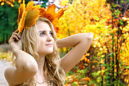 portrait of beautiful woman in autumn park with leaves photo