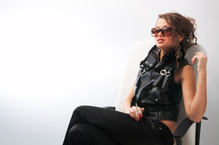 sunburned: glamour girl sits in white leather chair in  sunglasses and with cigarette in her arm
