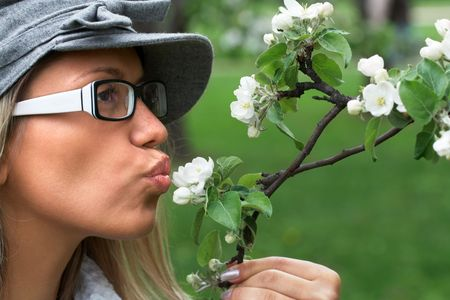 close-up portrait of girl in nature holding the apple tree branch with white flowers photo