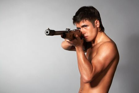 young naked man with rifle isolated on gray photo