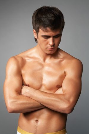 naked muscular young man isolated on gray  photo