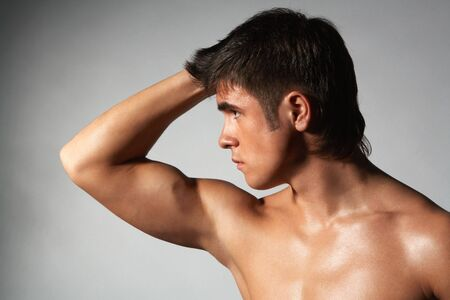 close-up portrait of young naked muscular athlete; isolated on gray  photo