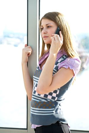 closeup portrait of girl speaking by mobile phone near window photo