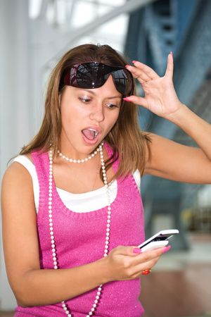 young lady is reading unexpected SMS and very surprised photo