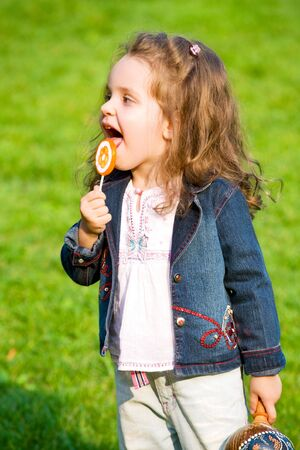 closeup portrait of little girl with lollipop photo