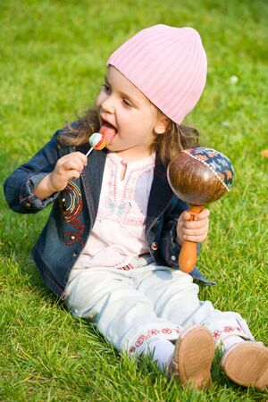 closeup portrait of child with lollipop on green grass
