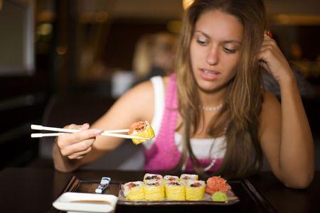 closeup portrait of girl with sushi in dark restaurant interior photo