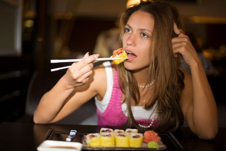 closeup portrait of girl with sushi in dark restaurant interior photo
