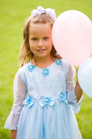 portrait of little girl in blue dress on the green grass with balloons photo