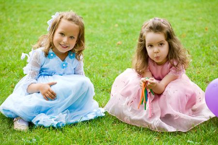 two little girls are sitting and playing on green grass photo