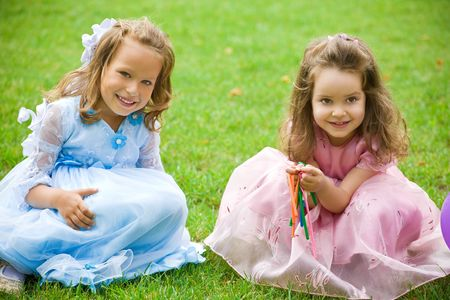 princess dress: two little girls are sitting and playing on green grass Stock Photo