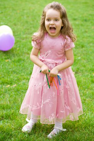 little girl in pink dress is crying on green grass