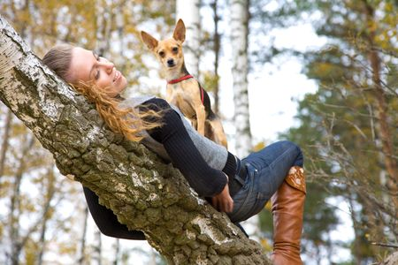 young adult girl with small doggy in autumnal park; dog isnt in focus photo