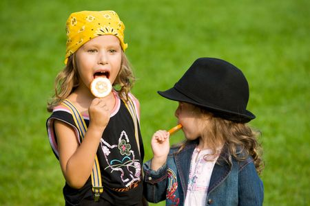 two little girl on green lawn with round lollipops photo