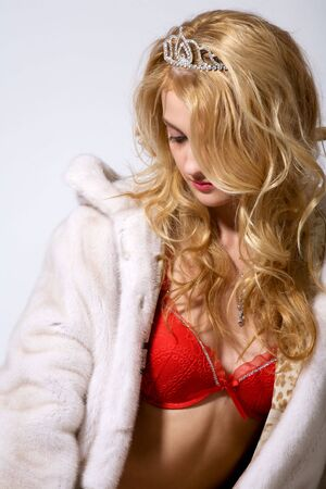 portrait of young woman in white fur coat and red lingerie on grey photo
