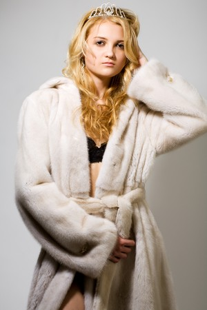 portrait of young woman in white fur coat and black bra on grey photo