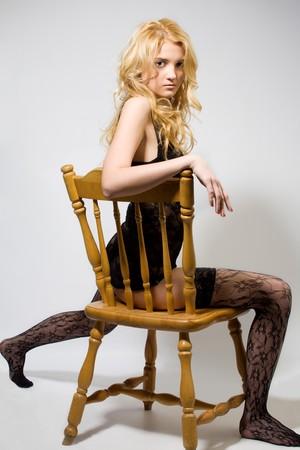 striptease women: blond is dancing striptease on chair