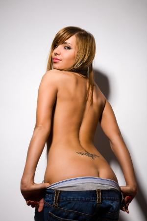 voluptueuse: sexy jeune femme se d�shabille sur le gris
