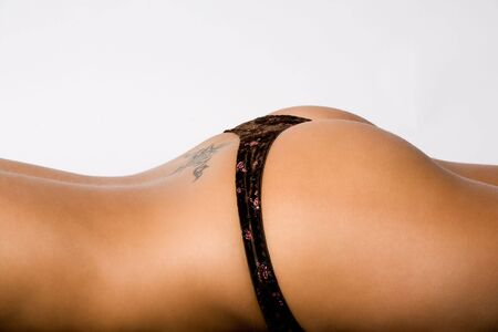 laying on back: part of beautiful young female body with tattoo on back