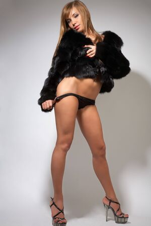young pretty girl in black fur coat,lingerie and high-heeled shoes on gray