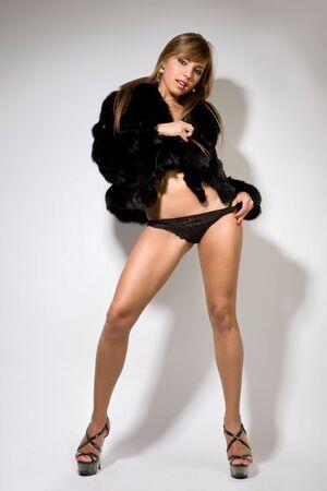 modelos desnudas: mujer joven rubia sexy en negro abrigo de piel en los zapatos de tac�n alto Foto de archivo