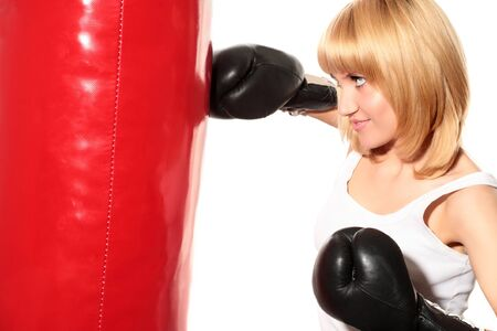 portrait of yong blond woman training in boxing on red panching bag photo