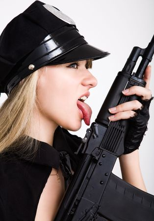 portrait of young sexy woman licking with tongue black tommy gun photo