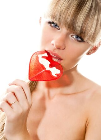 lick: close-up portrait of young sexy blond woman sucking lollipop isolated on white