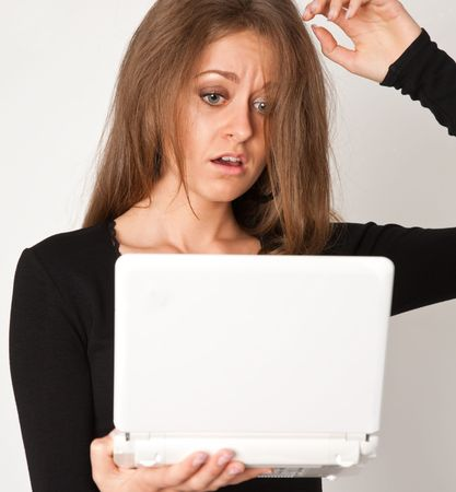 portrait of young business woman with white laptop on gray photo