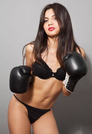 erotic portrait of young brown hair woman in black boxing gloves and lingerie Stock Photo - 5732019