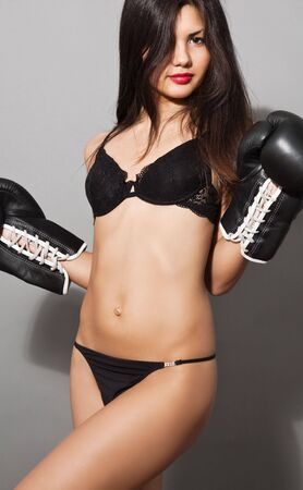 erotic portrait of young brown hair woman in black boxing gloves and lingerie Stock Photo - 5748683